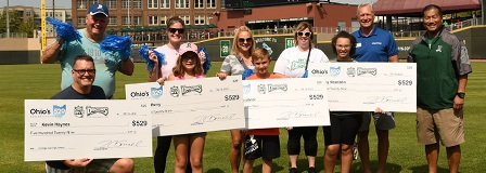 Families standing on baseball field with oversized checks