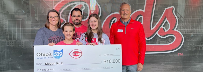 Family holding oversized check in front of Cincinnati Reds signage