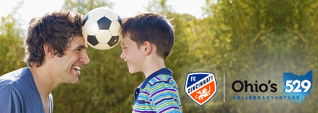 Father and young son balance soccer ball between their heads