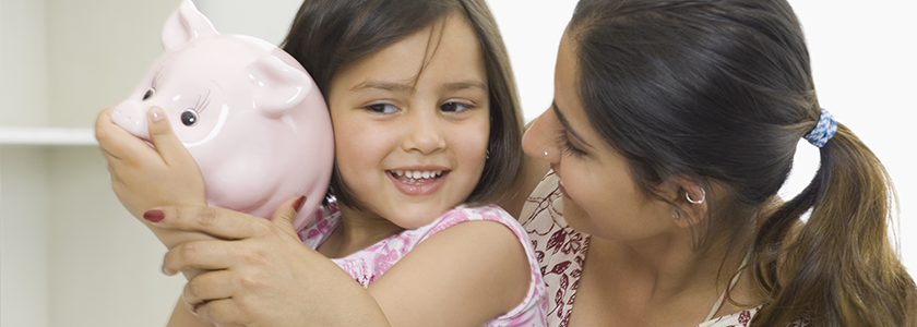 Mom smiling at daughter who is shaking a pink piggy bank