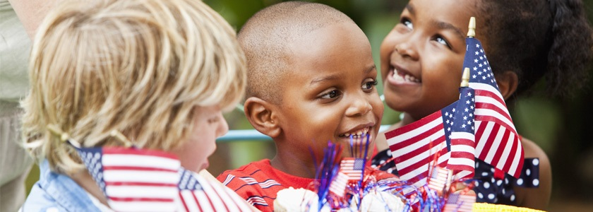 Smiling children celebrating with American flags