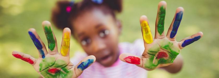 Little girl holding up her ten painted fingers