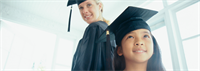 High school graduate and 5th grade graduate dressed in caps and gowns