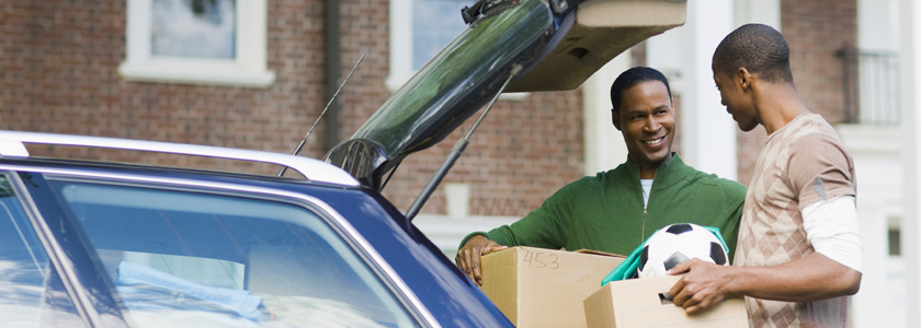 Father and son unpacking car as son heads off to college