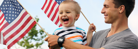 Father holding laughing son while holding small American flags