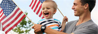 Father smiling at laughing son while they hold small American flags