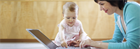 Mom smiling at baby playing with laptop keyboard