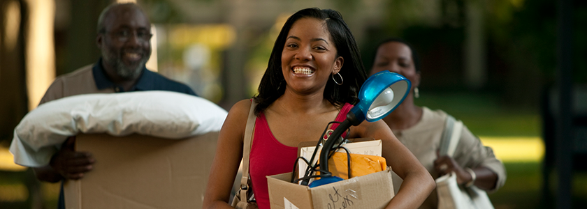 Grinning daughter and parents walks towards college dorm with boxes to move in