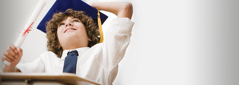 Younger boy wearing a graduation cap looking towards the sky