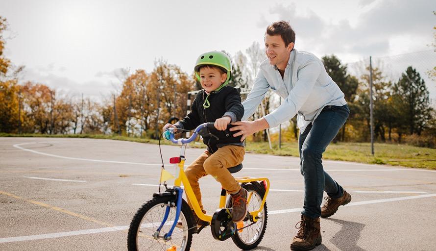 man pushing boy on bike