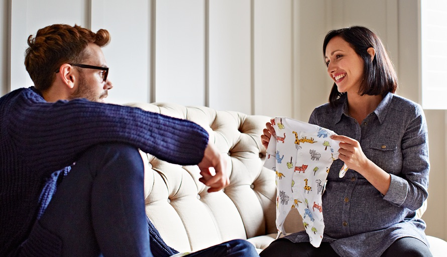 woman showing man baby outfit